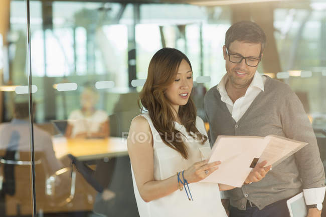 Business people reading paperwork in office — Stock Photo