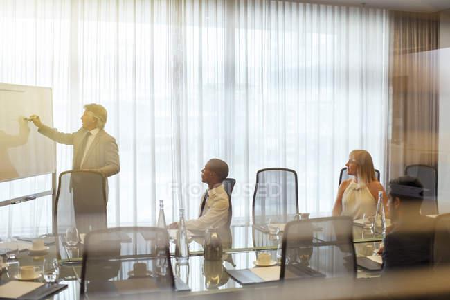 Uomo d'affari maturo che dà presentazione ai colleghi in sala conferenze — Foto stock
