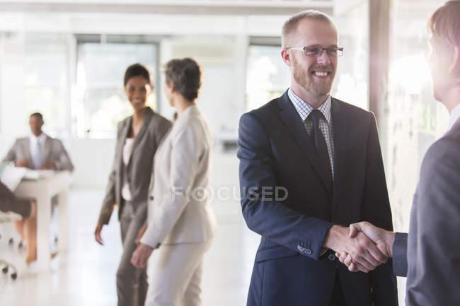 Мужчины пожимают руки, коллеги на заднем плане — стоковое фото