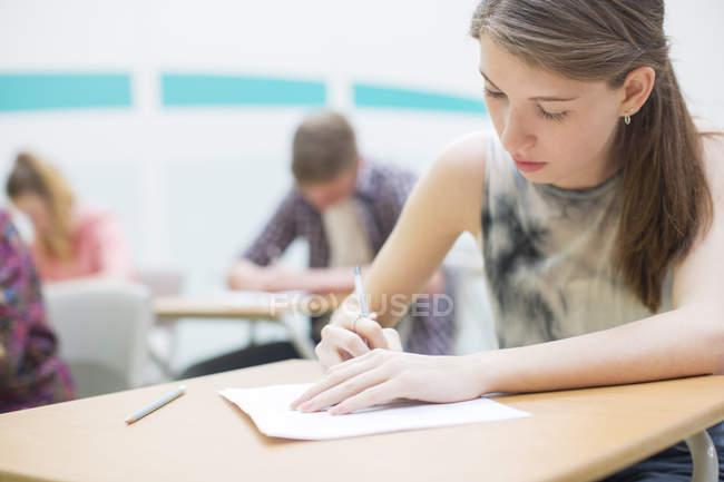 Studenti che scrivono il loro esame GCSE in classe — Foto stock