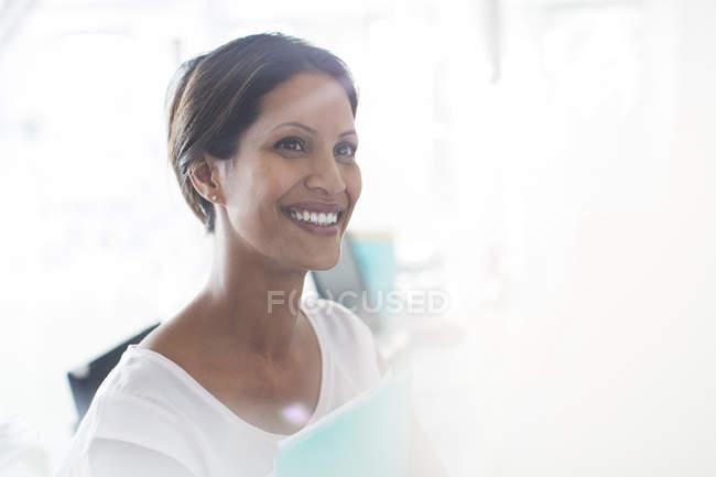 Ritratto di donna sorridente in possesso di documenti in carica — Foto stock