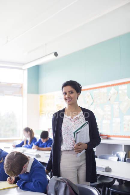Portrait of smiling female teacher and elementary school children in classroom — Stock Photo
