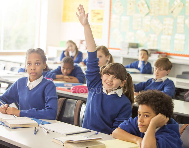 Bambini della scuola elementare in aula durante la lezione, sorridente ragazza solleva la mano — Foto stock
