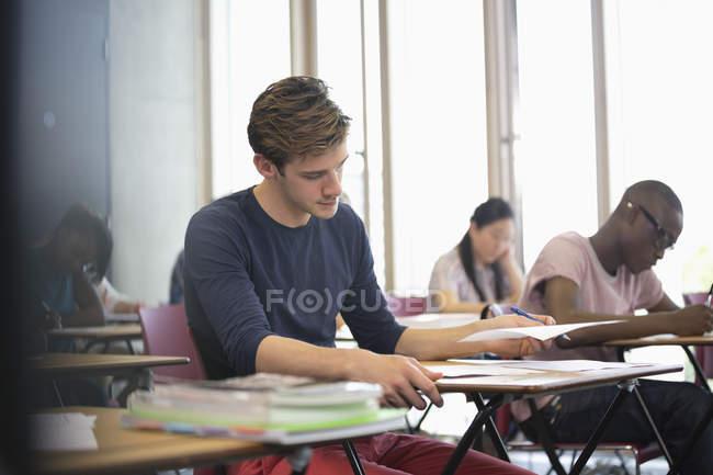 Studente universitario sostenere l'esame, gli studenti in background scrittura — Foto stock