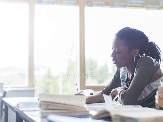 Studente donna che scrive alla scrivania in classe — Foto stock