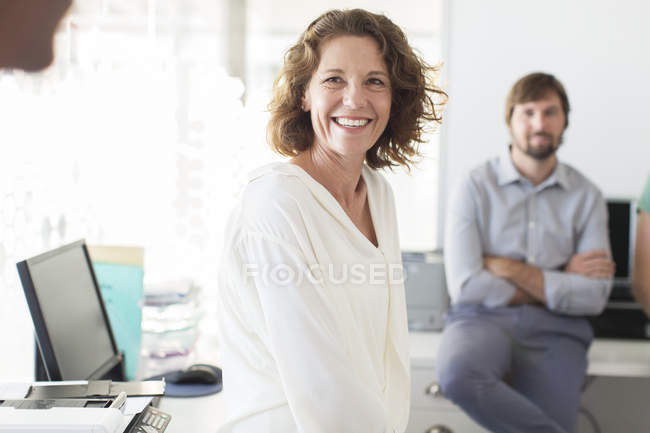 Portrait of businesswoman in office, colleague in background — Stock Photo