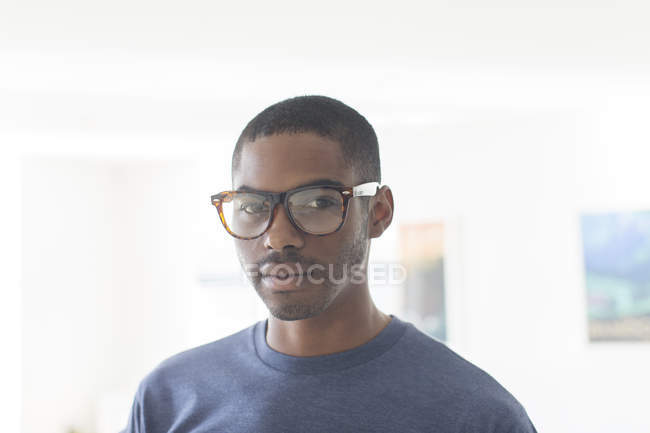 Portrait of young businessman wearing glasses standing in office — Stock Photo