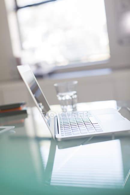 Открытый ноутбук и стакан воды на стеклянном столе в офисе — стоковое фото