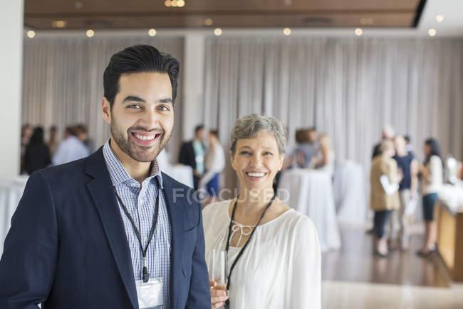 Портрет мужчины и женщины, стоя в фойе конференц центр улыбается — стоковое фото