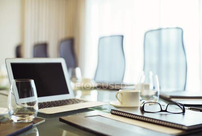 Laptop, Brille und Tagebuch auf Konferenztisch im leeren Konferenzraum — Stockfoto