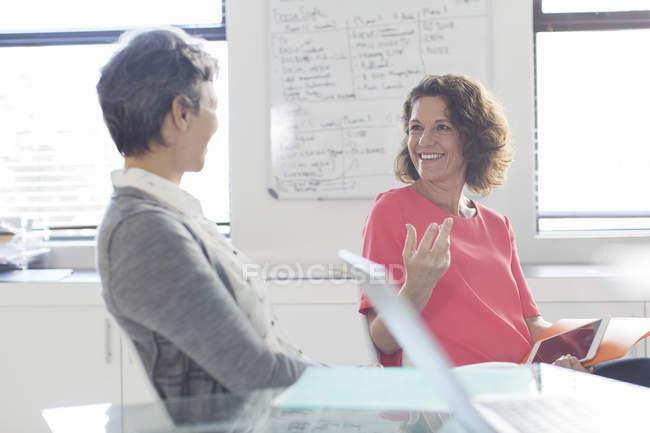 Две женщины улыбаясь, говорить в офисе, доска в фоновом режиме — стоковое фото