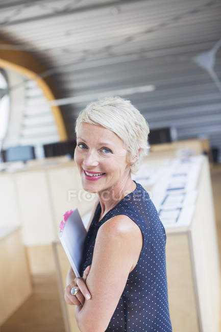 Businesswoman holding paperwork in office — Stock Photo