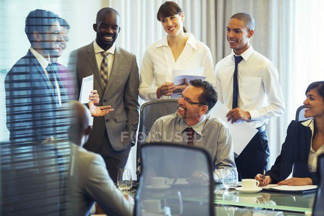 Деловые люди улыбаются в зале во время деловой встречи — стоковое фото