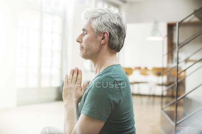 Homme plus âgé méditant à l'intérieur — Photo de stock