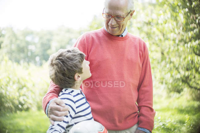 Grandfather and grandson hugging outdoors with ball — Stock Photo