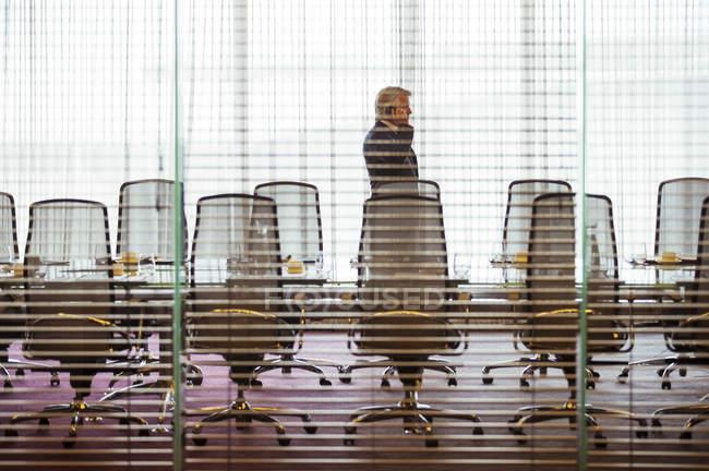 Стоящий и пользующийся мобильным телефоном бизнесмен в конференц-зале — стоковое фото