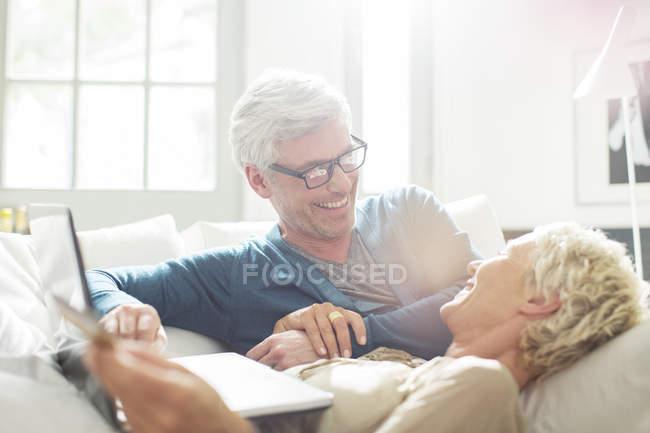 Пари дорослих разом відпочиваючи на диван — стокове фото