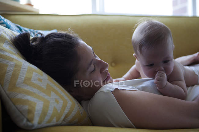 View of mother lying on sofa with little baby sucking thumb — Stock Photo