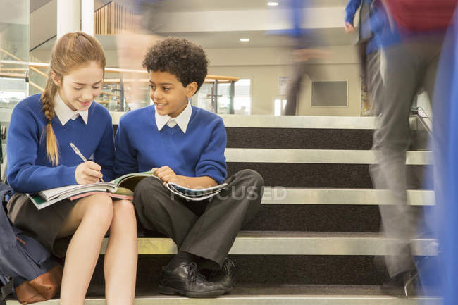 Elementary school children wearing school uniforms sitting on steps and writing in textbooks — Stock Photo