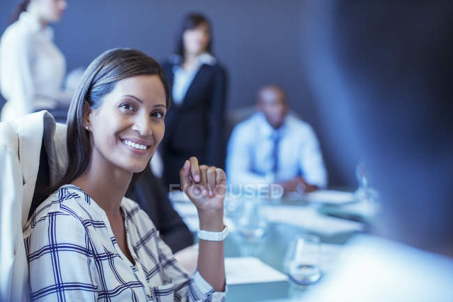 Retrato de empresária adulta média sentada na sala de conferências e olhando para longe — Fotografia de Stock