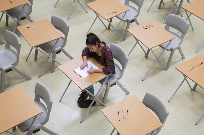 Vista elevata di studentessa sola che scrive il loro esame GCSE in classe — Foto stock