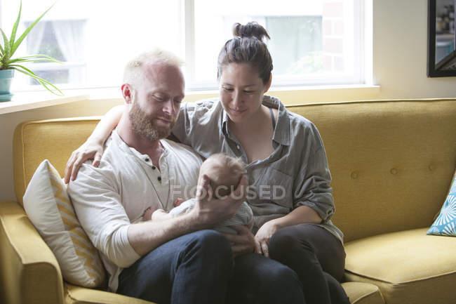 Parents souriants et tenant petit bébé — Photo de stock