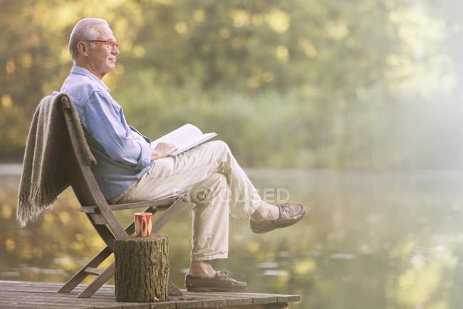 Вид сбоку пожилого человека, читающего книгу на причале у озера — стоковое фото