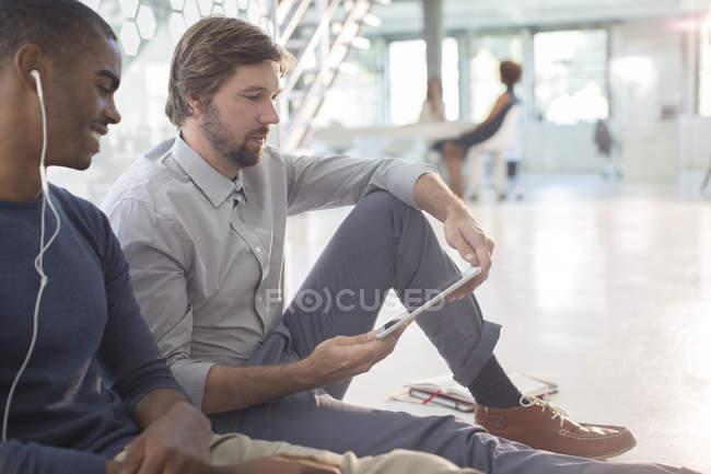 Two businessmen using digital tablet and earphones sitting on floor in modern office — Stock Photo