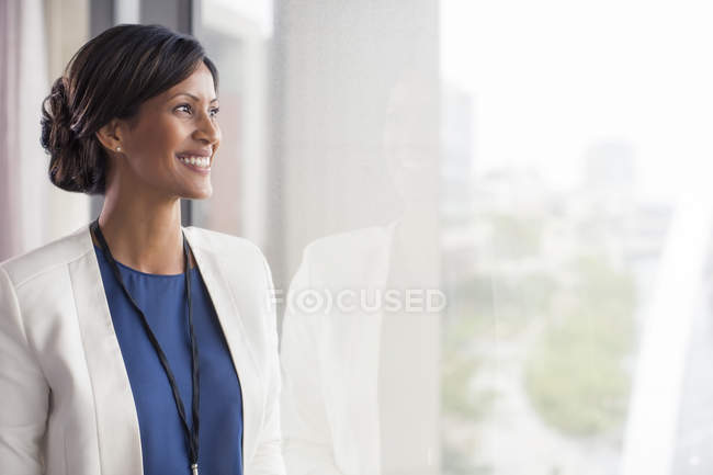 Portrait de femme souriante mi-adulte regardant par la fenêtre — Photo de stock