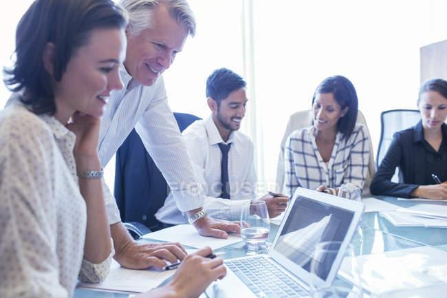 Деловые женщины и бизнесмены сидят за столом для конференций, пользуются ноутбуком и улыбаются — стоковое фото