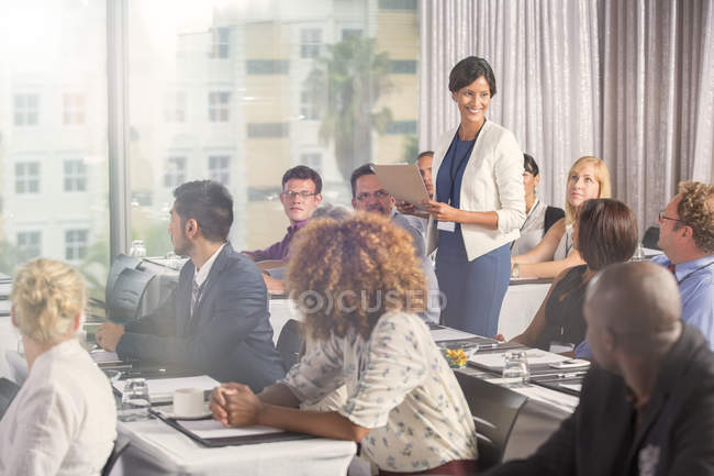 Group of people sitting at desks and listening to speaker — Stock Photo