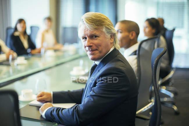 Retrato de homem de negócios sentado à mesa de conferência na sala de conferências — Fotografia de Stock