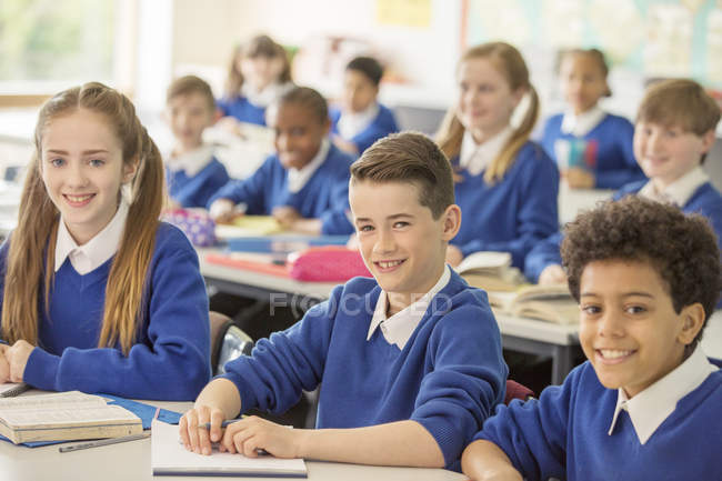 Elementary school children smiling in classroom — Stock Photo