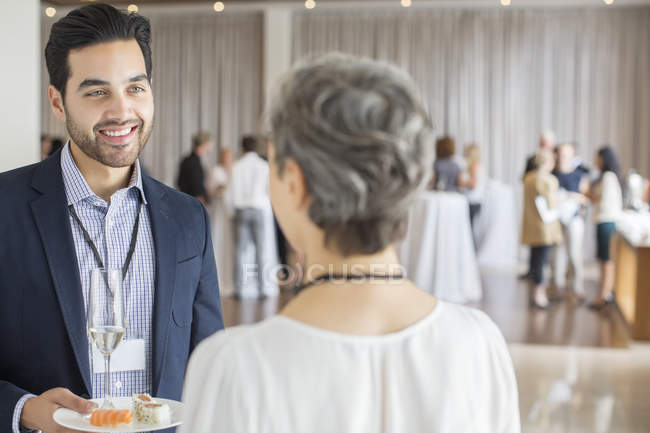 Businessman talking to businesswoman during reception in conference room, holding plate and champagne flute — Stock Photo