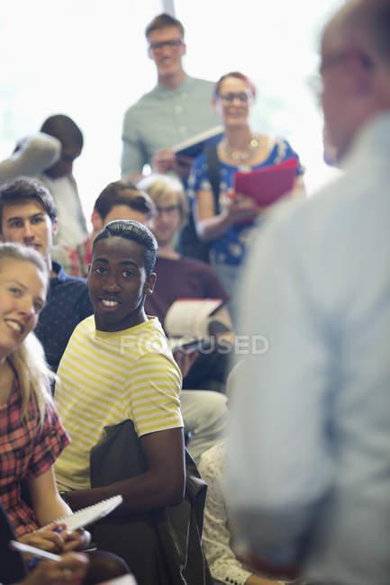 Зосереджено студентів, слухаючи професор на семінарі в класі — стокове фото