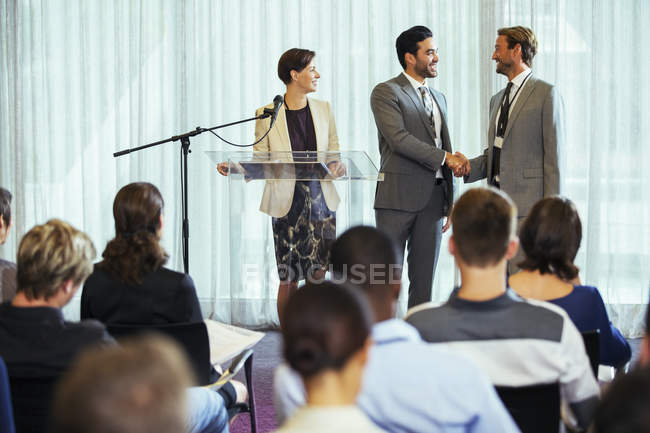 Businessmen shaking hands during presentation in conference room, businesswoman smiling — Stock Photo