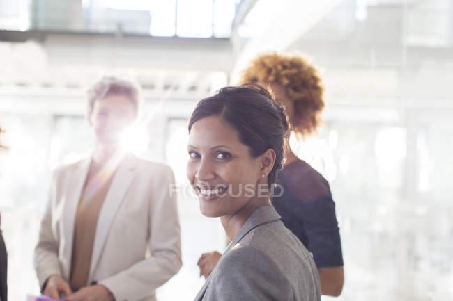 Портрет улыбающейся деловой женщины с коллегами на заднем плане — стоковое фото