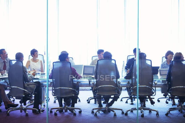 Business people having meeting in conference room, sitting with laptops and discussing — Stock Photo