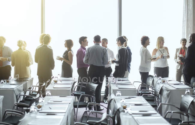 Group of people standing by windows of conference room, socializing during coffee break — Stock Photo