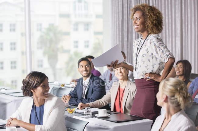 Предприниматель, стоя с документом в руке во время презентации в зале — стоковое фото