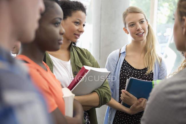 Studenti universitari con libri in piedi nella conversazione del corridoio — Foto stock