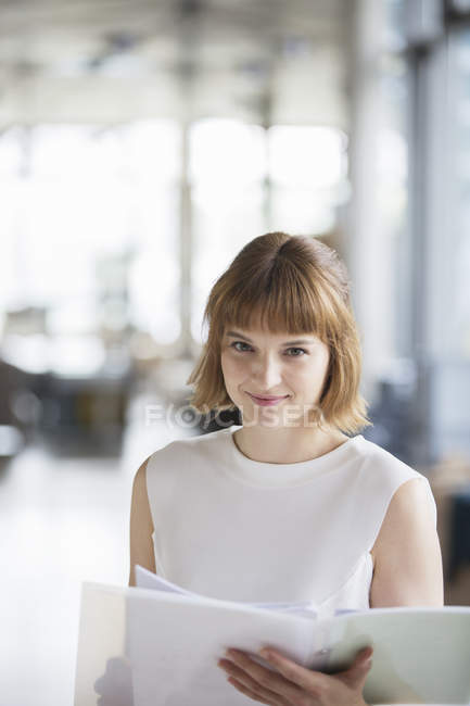 Businesswoman reading paperwork in office — Stock Photo