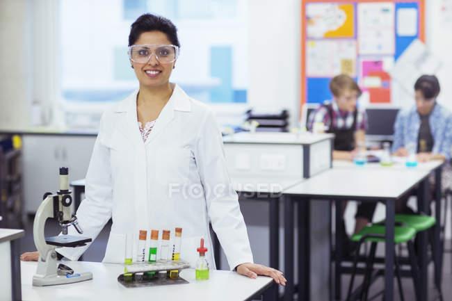 Retrato de una profesora sonriente con gafas protectoras, parada detrás del escritorio con microscopio y tubos de ensayo en rack, estudiantes en segundo plano - foto de stock