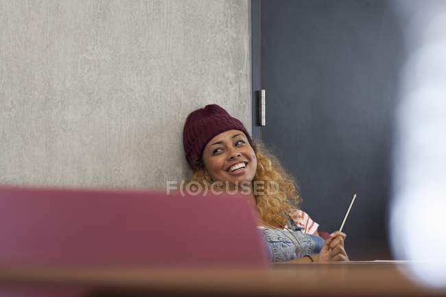Smiling university student relaxing during break in classroom — Stock Photo