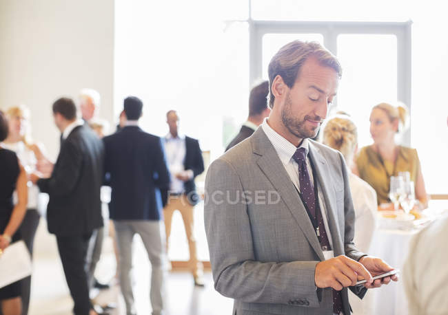Mid adult businessman text messaging in office — Stock Photo