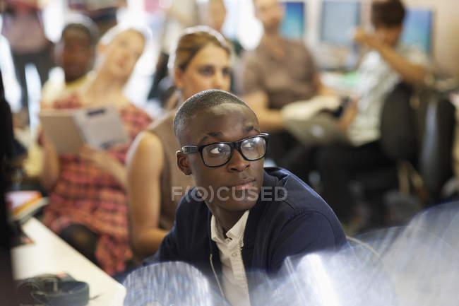 Étudiant à l'université à l'écoute du séminaire informatique, étudiants assis en arrière-plan — Photo de stock