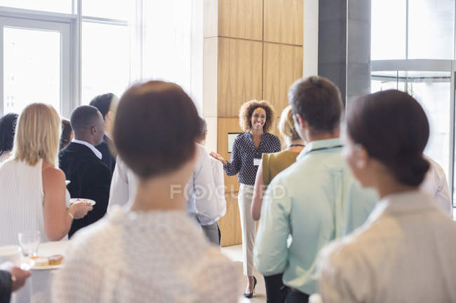 Business people standing in office hall holding trays with cakes and drinking water — Stock Photo