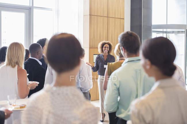 Empresários de pé no corredor do escritório segurando bandejas com bolos e água potável — Fotografia de Stock