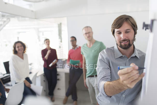 Group of people having meeting in office, man writing on flipchart — Stock Photo