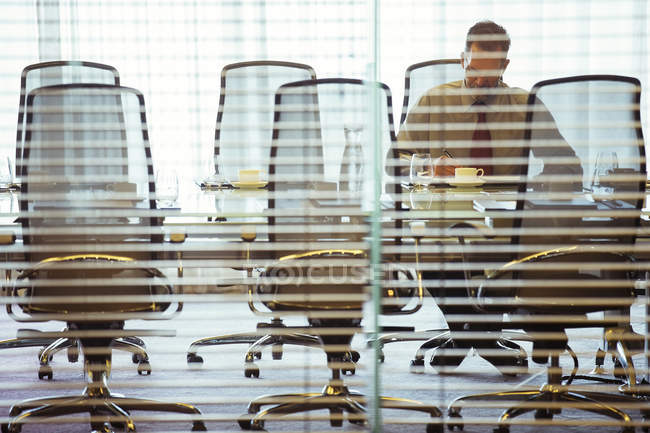 Businessman sitting behind blinds in conference room — Stock Photo